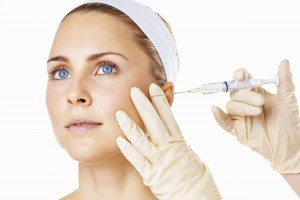 Detail shot of a blue eyed woman receiving Botox injection against white background